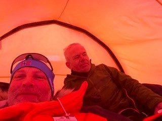 Claus og Arne i teltet. Billedet er helt orange på grund af teltets orange farve.