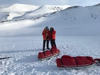 Claus og Arne ved pulkene med nogle fotte sneklædte bjerge i baggrunden.